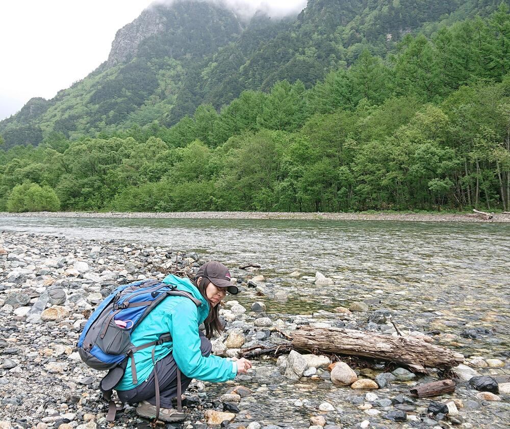 Yukiko near a stream in front of a mountain in Kamokochi, Japan