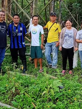 7 people standing in front of a lush trees and forest in the Philippines. The people are smiling and posing for the picture.